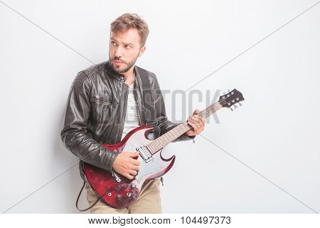 young guitarist playing his red electric guitar and looks to his side away from the camera