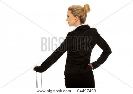 Young businesswoman with wheeled suitcase.
