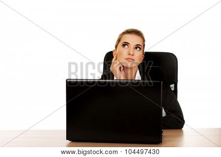 Young businesswoman behind the desk, using laptop.