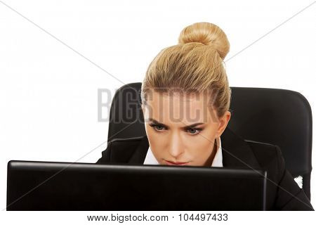 Surprised and curious business woman cannot believe what she sees in the laptop screen.