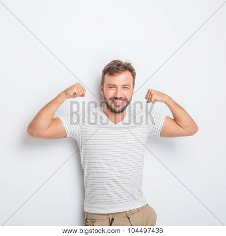 laughing young fit casual man showing you how strong he is by flexing his muscles in studio