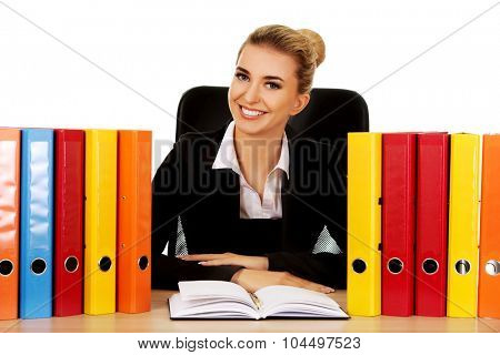Smile businesswoman with binders by a desk.