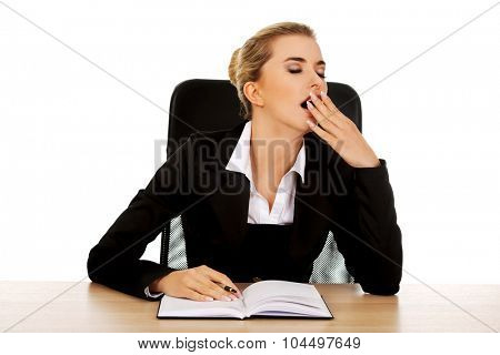 Yawning businesswoman writing note by a desk.