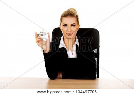 Businesswoman by a desk holding a toy plane.