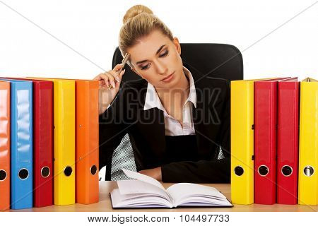 Exhausted businesswoman with binders behind the desk.