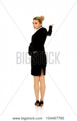 Young businesswoman pointing at something.