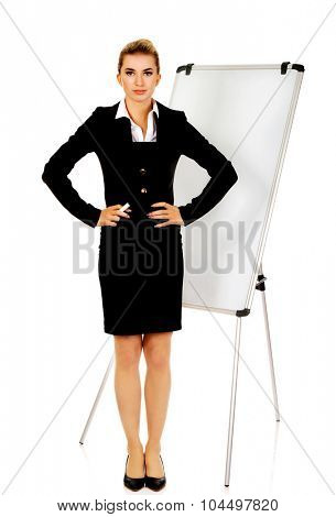 Young business woman standing nex to the white board.