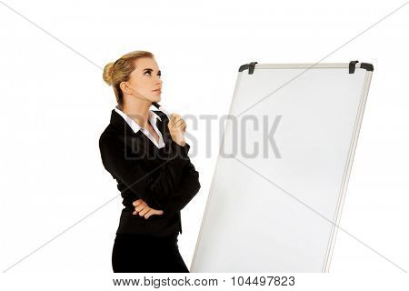Thinking business woman standing nex to the white board.