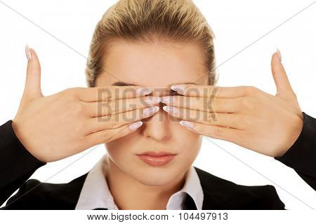 Beautiful woman covering her eyes with her hands. See no evil concept.