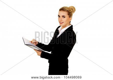 Young businessoman holding notebook and writes something.