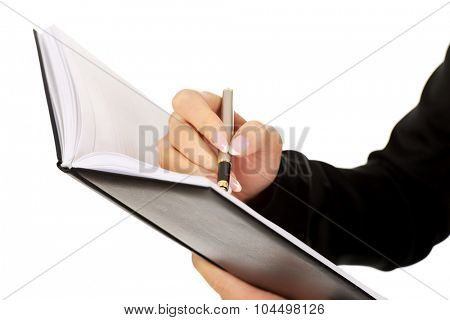 Woman holding notebook and writes something.