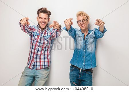 two excited young casual men pointing fingers to the camera in studio