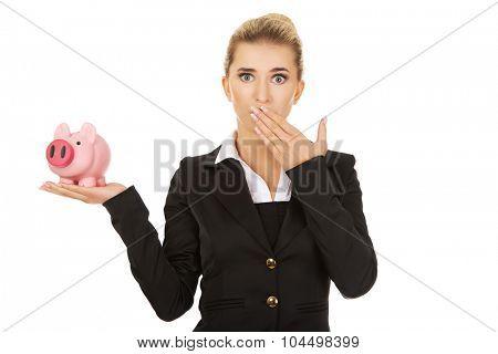 Surprised businesswoman holding a piggybank.