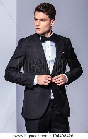 Attractive business man looking to his side while unbuttoning his tuxedo.