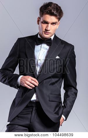 Young business man unbuttoning his jacket while holding one hand in his pocket.