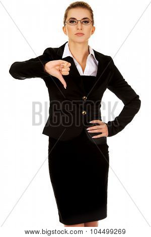 Unhappy young businesswoman with thumbs up.