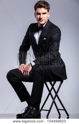 Full body picture of a young business man sitting on a stool while holding one hand on his leg.
