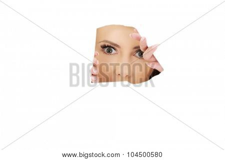 Businesswoman looking through tear paper sheet.
