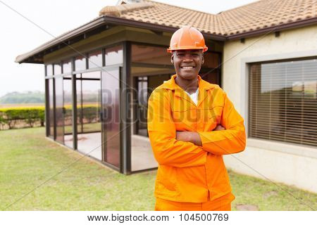 handsome african construction worker standing outside the house