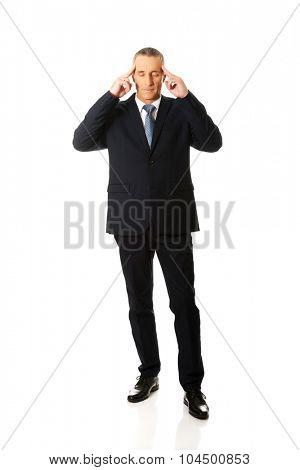 Mature thoughtful businessman touching head.