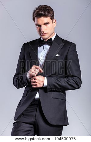 Young handsome business man looking at the camera while fixing his sleeve.