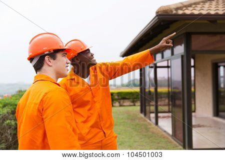 professional multiracial male construction workers pointing at house before renovation