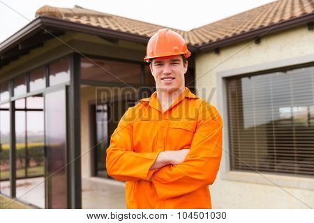young construction worker with arms crossed in front of a house