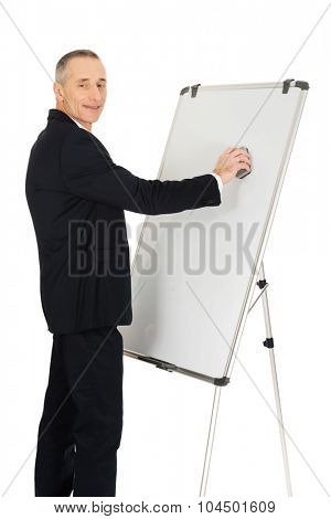 Mature businessman cleaning a flip chart.