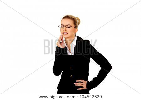 Young businesswoman suffering from toothache.