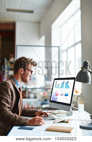 Modern young employee analyzing financial data in office