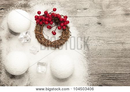 Christmas background with snowballs, ice cubes, holiday wreath, and red berries on wooden background with snow