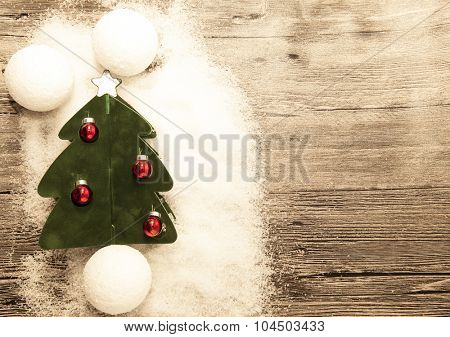 Christmas card with red Christmas balls, snowballs, winter snow and star on wooden background.