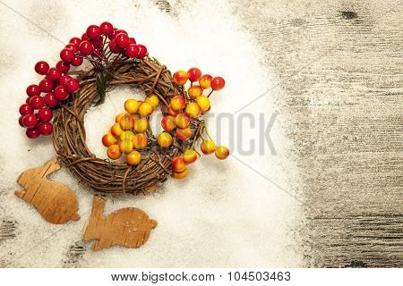 Christmas card with winter snow, christmas wreath with red and yellow rowan berries and small rabbits from birch bark on wooden background.
