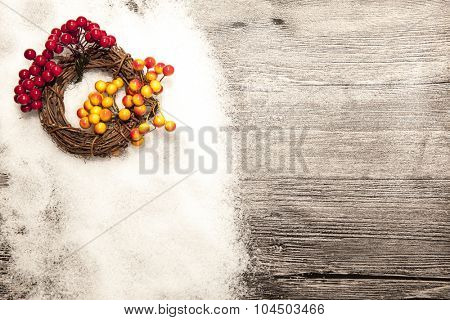 Christmas card with winter snow and christmas wreath with red and yellow rowan berries on wooden background.
