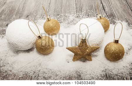 Glittering gold Christmas balls, snowballs, winter snow and star on wooden background.