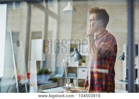 Businessman in casualwear talking on the phone in office