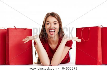 Ecstatic young woman looking at camera between red paperbags