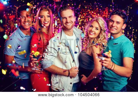 Group of joyful friends looking at camera at party
