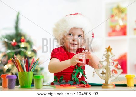 child girl making christmas decorations with play clay toy
