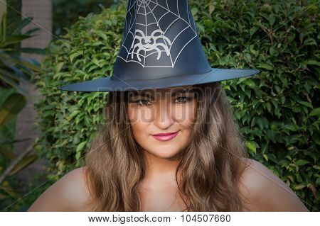 Beautiful Young Witch With Green Eyes And Hat Outdoors