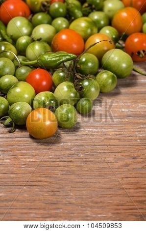 tomatoes and peppers on a wooden table