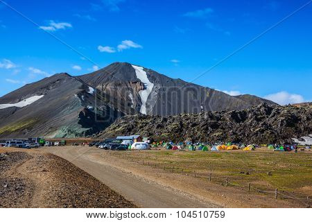 Rhyolite mountains surround the flat valley of National Park Landmannalaugar. Big tourist camp is located in the valley of the park