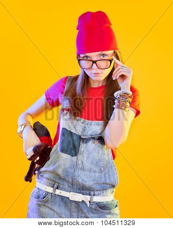 Portrait Of Funny Girl In Glasses And Red Caps. Seriously Looking At Viewer. Isolation On A Yellow