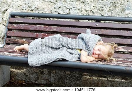 Cute little girl in fur coat sleeping on the bench in park