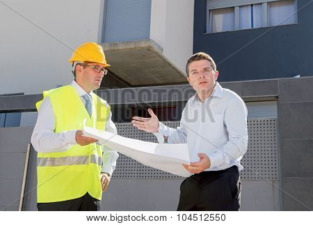 Unhappy Customer In Stress And Constructor Foreman Worker Arguing Outdoors On New House Building