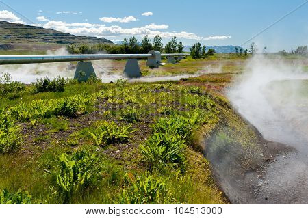 Pipes near geothermal power plant and a steaming hot river, Iceland