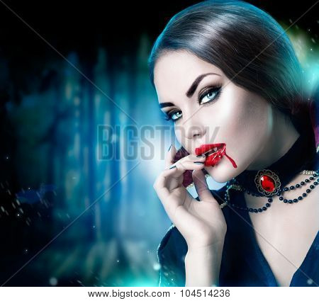 Beautiful Halloween Vampire Woman portrait. Beauty Sexy Vampire lady with blood on her mouth looking at camera. Fashion Art design. Attractive model girl in Halloween costume and make up