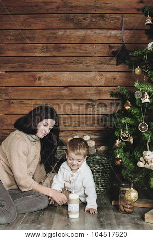 Mother with her 3 years old son celebrating holidays near Christmas tree, farm house design