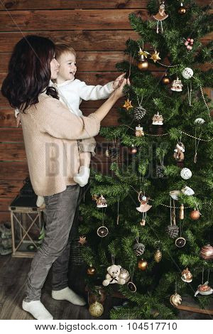 Mother with her 3 years old son decorating Christmas tree together, farm house design
