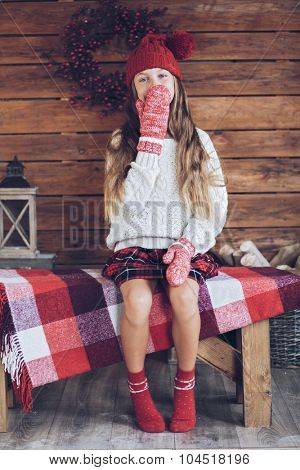 Child sitting on a vintage bench on rustic wooden background, Christmas decorated farmhouse interior.